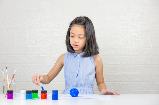 Śliczna mała dziewczynka uczy się malowania kolorem na piłce z pianki