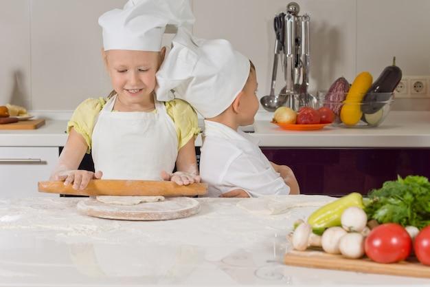 Śliczna Mała Dziewczynka Uczy Się Piec Premium Zdjęcia
