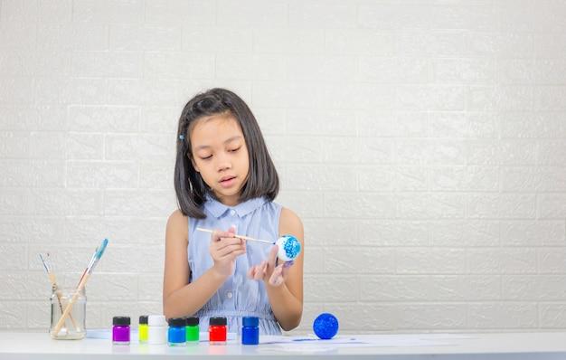 Śliczna mała dziewczynka uczy się układu słonecznego z malowaniem na piłce z pianki