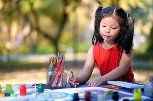 Śliczna mała dziewczynka uczy się w boisku.