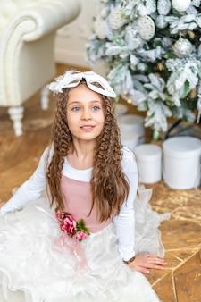 Śliczna mała dziewczynka uśmiecha się i pozuje z dekoracjami świątecznymi