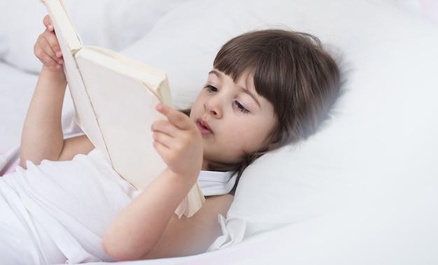 Śliczna mała dziewczynka uśmiecha się leżąc w przytulnym białym łóżku z koncepcją odpoczynku i snu dzieci