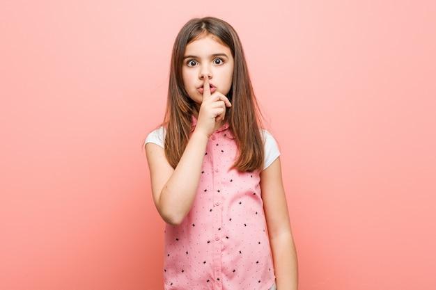 Śliczna mała dziewczynka utrzymuje sekret lub prosi o ciszę.