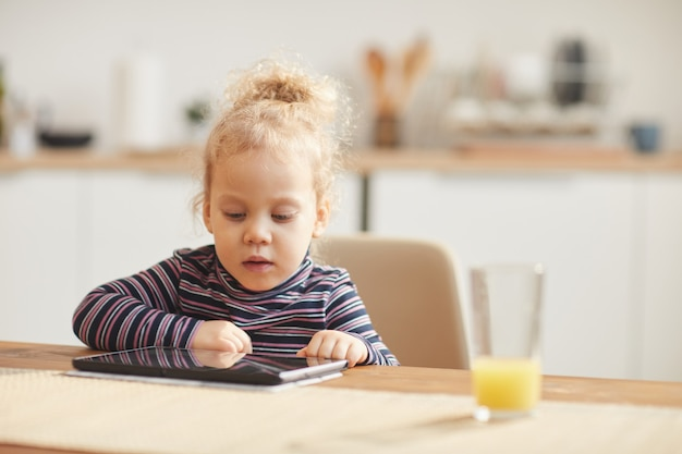 Śliczna mała dziewczynka używa cyfrowej pastylkę