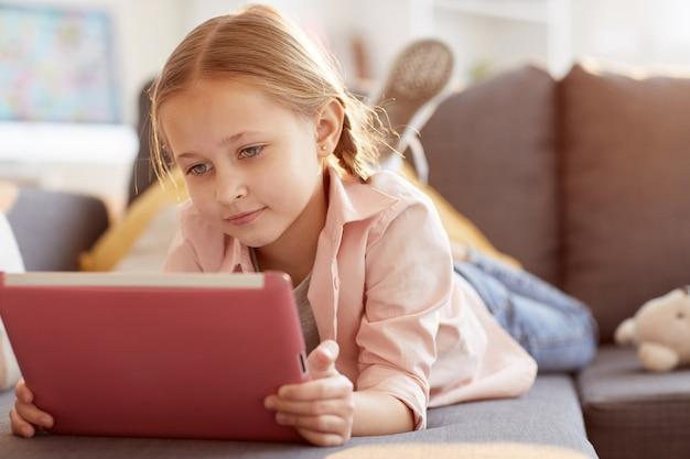 Śliczna mała dziewczynka używa pastylkę