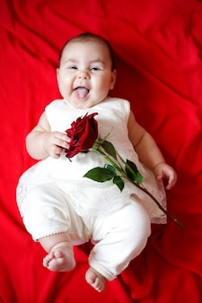 Śliczna mała dziewczynka w białej sukni z czerwoną różą