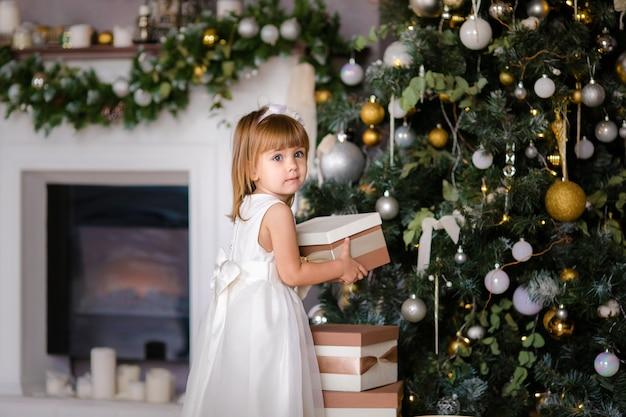 Śliczna mała dziewczynka w białej sukni z dużymi teraźniejszość blisko choinki