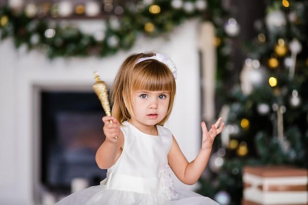 Śliczna mała dziewczynka w białej sukni z ładnym wiankiem blisko choinki