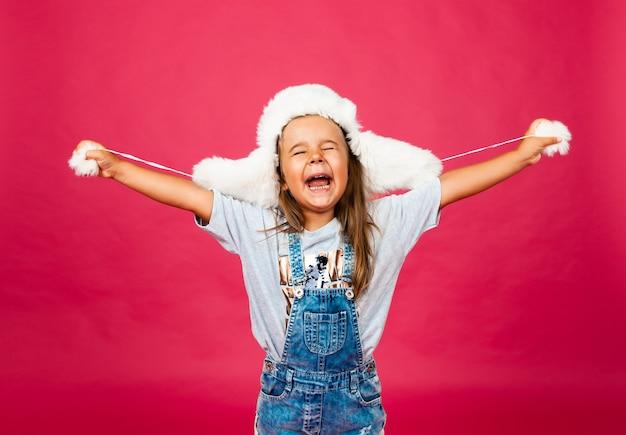 Śliczna mała dziewczynka w białym futrzanym kapeluszu na różowej ścianie. koncepcja mody.