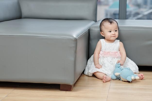 Śliczna mała dziewczynka w bufiastej sukience siedzi na podłodze i bawi się zabawkami