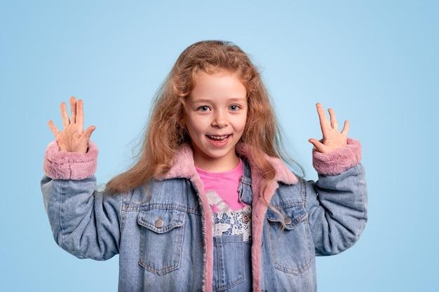 Śliczna mała dziewczynka w ciepłej dżinsowej kurtce, trzymając ręce uniesione, pokazując dłonie i uśmiechając się