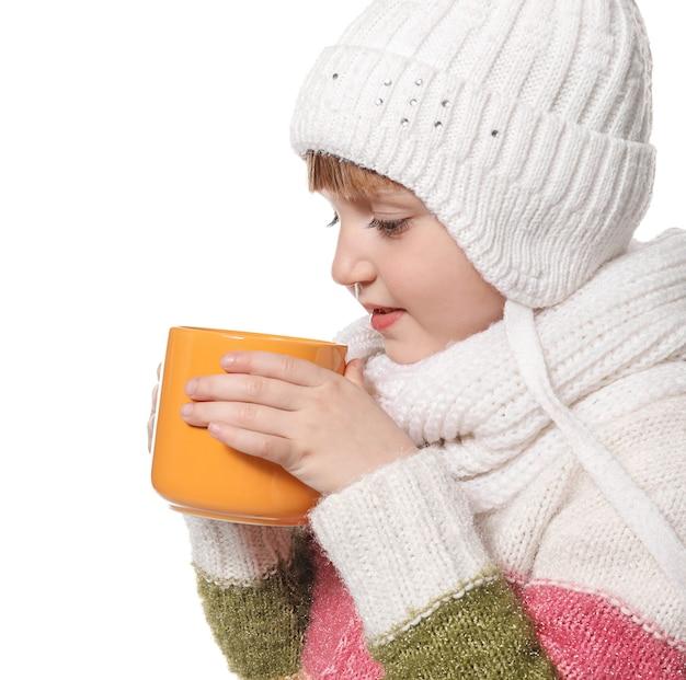 Śliczna mała dziewczynka w ciepłych ubraniach i filiżance gorącego napoju kakaowego na białym