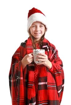 Śliczna mała dziewczynka w czapce świętego mikołaja i filiżankę gorącej czekolady na białym tle