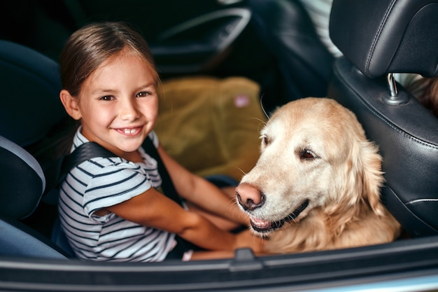 Śliczna mała dziewczynka w foteliku samochodowym chronionym pasami bezpieczeństwa wraz ze swoim przyjacielem psem labradorem jedzie na weekend. wypoczynek, podróże, turystyka.