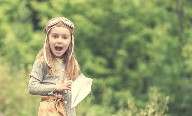 Śliczna mała dziewczynka w hełma pilocie z papierowym samolotem