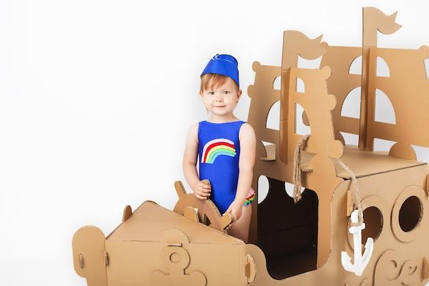 Śliczna mała dziewczynka w jasnym kostiumie kąpielowym bawiąca się kartonowym statkiem