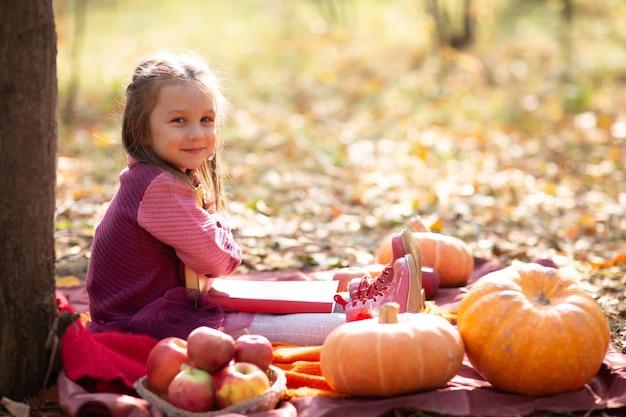 Śliczna mała dziewczynka w jesienny park z książkami i pomarańczowymi liśćmi i żółtą dynią.