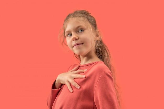 Śliczna mała dziewczynka w koralowej sukience z długimi włosami, uśmiechając się
