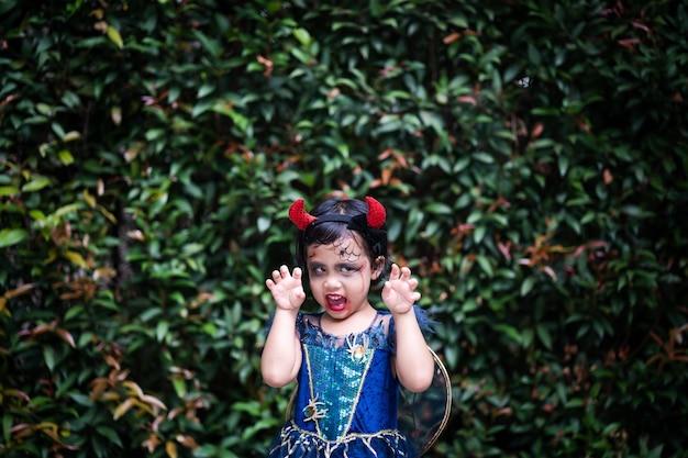 Śliczna mała dziewczynka w kostiumie na halloween z wyrazem twarzy stojąca na zewnątrz