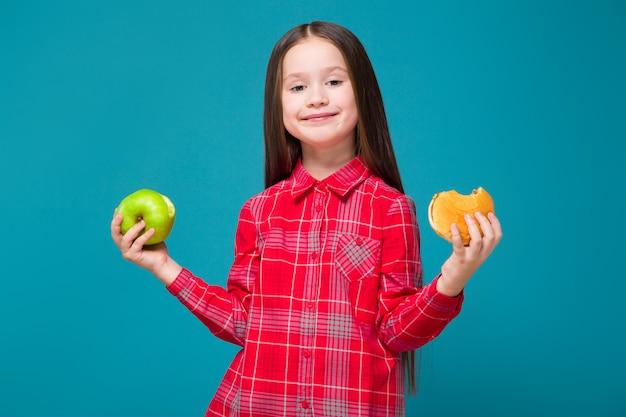 Śliczna, mała dziewczynka w kraciastej koszuli z brunetką trzymająca burgera