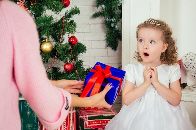 Śliczna mała dziewczynka w ładnej sukience z długimi kręconymi blond włosami trzymająca w domu pudełko z prezentem w pobliżu choinki z prezentami i girlandami oraz udekorowanym kominkiem