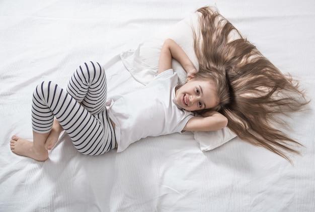 Śliczna mała dziewczynka w łóżku obudziła się rano.