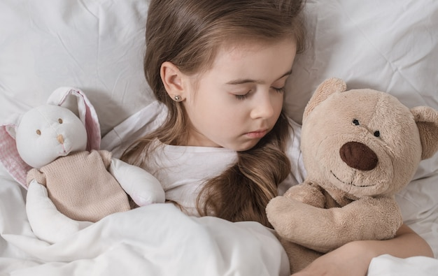 Śliczna mała dziewczynka w łóżku z miękką zabawką.