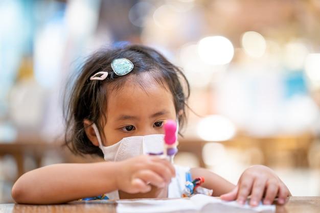Śliczna mała dziewczynka w masce ochronnej siedzi przy drewnianym stole w centrum handlowym