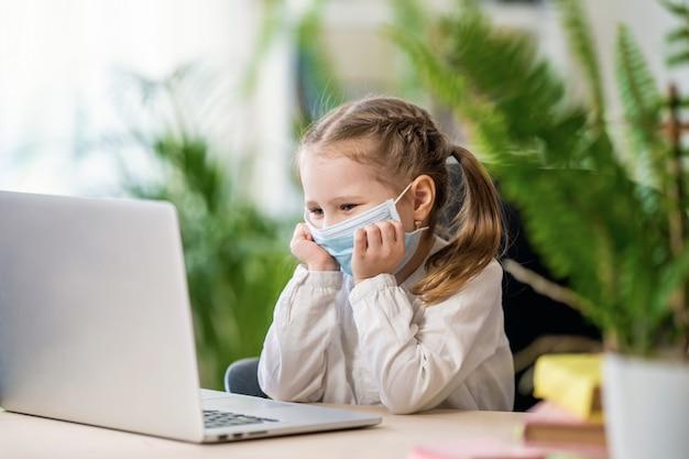 Śliczna mała dziewczynka w masce robi pracie domowej używać laptop