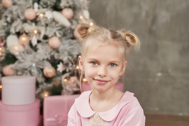 Śliczna mała dziewczynka w menchii sukni z bożenarodzeniową dekoracją
