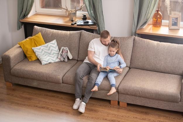 Śliczna mała dziewczynka w niebieskiej piżamie i jej ojciec czytający książkę, relaksując się na miękkiej wygodnej kanapie przy oknie w salonie