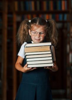 Śliczna mała dziewczynka w okularach stoi w bibliotece pełnej książek