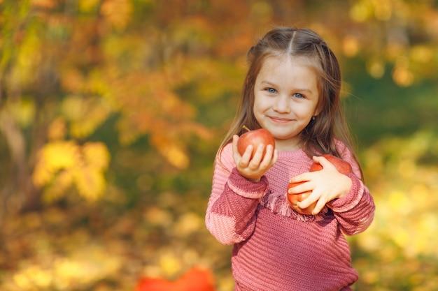 Śliczna mała dziewczynka w parku jesień trzymać w rękach czerwone jabłka.
