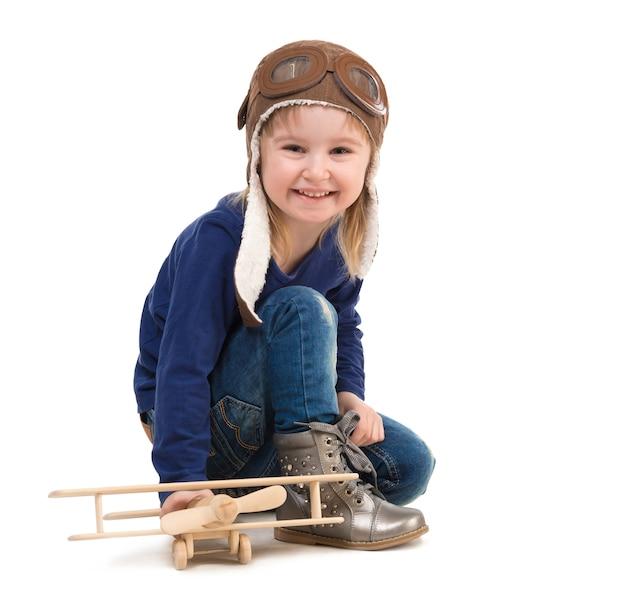 Śliczna mała dziewczynka w pilotowym kapeluszu z drewnianym samolotem