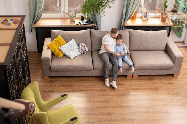 Śliczna mała dziewczynka w piżamie i jej kochający ojciec siedzący na kanapie w salonie i czytający bajki podczas kwarantanny