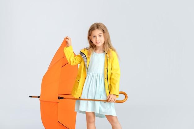 Śliczna mała dziewczynka w płaszczu i parasolem