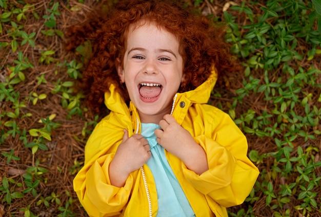 Śliczna mała dziewczynka w płaszczu leżącym na zielonej łące