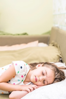 Śliczna mała dziewczynka w polka kropki podkoszulku bez rękawów dosypianiu na łóżku