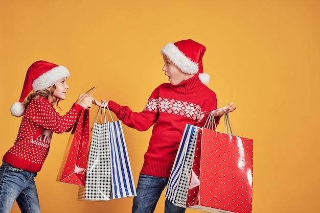 Śliczna mała dziewczynka w santa kapeluszowym wiszącym torba na zakupy z bożenarodzeniowymi prezentami na ręce zdziwiona chłopiec podczas wakacyjnego świętowania przeciw żółtemu tłu