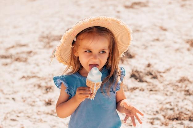 Śliczna mała dziewczynka w słomkowym kapeluszu jedząca lody z miękkiego stopionego masła w szklance waflowej nad morzem