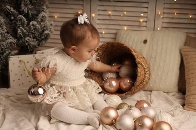 Śliczna mała dziewczynka w stroju noworocznym bawiąca się pudrową piłką noworoczną