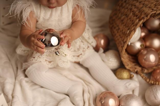 Śliczna mała dziewczynka w stroju świątecznym bawiąca się bombkami na choinkę