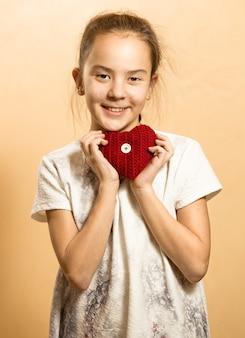 Śliczna mała dziewczynka w sukience pozuje z czerwonym dzianym sercem