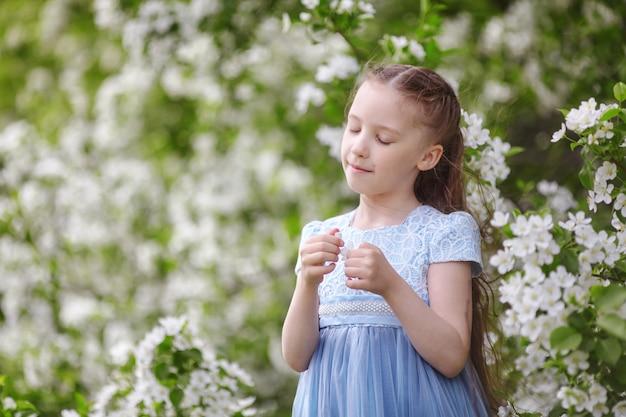 Śliczna mała dziewczynka w sukience w kwitnącym ogrodzie jabłoni na wiosnę