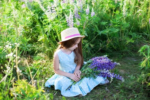 Śliczna mała dziewczynka w sukni i kapeluszu w polu łubiny. dziewczyna trzyma duży bukiet fioletowych łubinów w polu kwitnienia. kwitnące kwiaty łubinu. koncepcja natury. prowansja dzieciństwo. letni wypoczynek