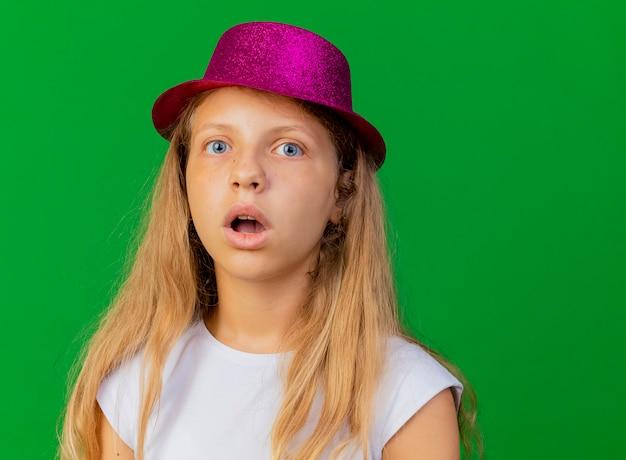 Śliczna mała dziewczynka w świątecznym kapeluszu zaskoczona i zdumiona