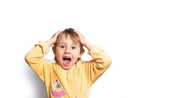 Śliczna mała dziewczynka w szlafroku pozuje zabawnie i zszokowana