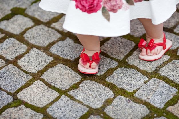 Śliczna mała dziewczynka w wieku 1 roku stawiająca pierwszy krok. śliczne nogi małego dziecka w czerwonych sandałach na ulicy z bliska
