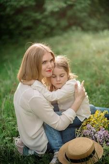 Śliczna mała dziewczynka w wieku 4 lat i jej piękna mama spacerują po parku wiosną