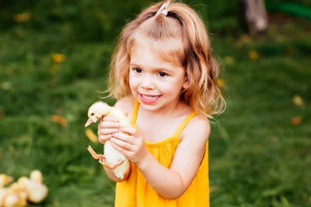 Śliczna mała dziewczynka w żółtej sukience trzyma w rękach kaczątko